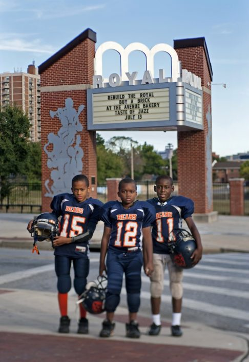 Youth in Baltimore stand beside a sign proposing rebuilding the Royal Theater.