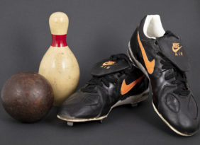 Duck pin bowling ball and pin and Orioles baseball cleats.
